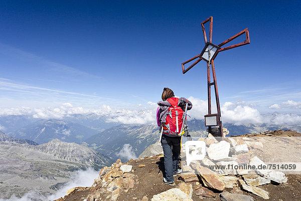 Bergsteiger am Gipfelkreuz auf dem Schneebigen Nock  Südtirol  Italien  Europa