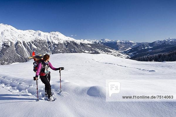 Schneeschuhwanderin beim Aufstieg zur Jagelealm  hinten das Ridnauntal  der Rosskopf und die Telfer Weißen  Südtirol  Italien  Europa