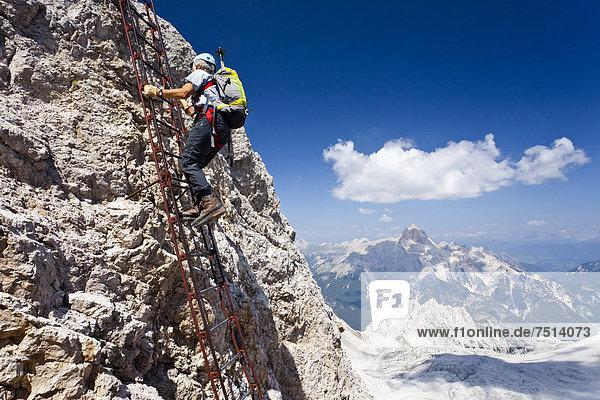 Bergsteiger beim Aufstieg über die Via ferrata Ivano Dibona  Klettersteig am Monte Cristallo zum Gipfel des Cristallino oberhalb von Cortina  hinten die Hohe Gaisl  Belluno  Dolomiten  Italien  Europa