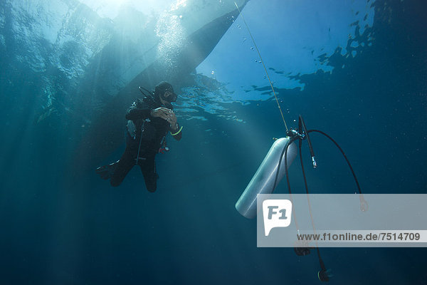 Diver with spare air tank during a decompression stop under a boat  Philippines  Asia