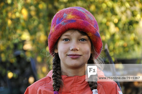 Portrait of a girl with braids  eight years old  wearing a colorful felt hat  Othenstorf  Mecklenburg-Western Pomerania  Germany  Europe