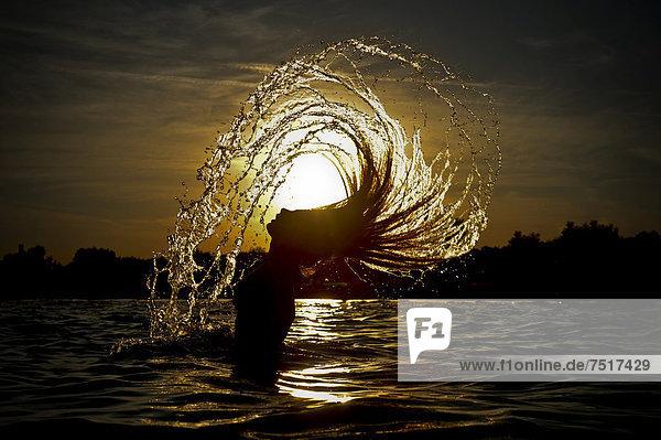 Junge Frau im Meer wirft ihre langen Haare mit einem Wasserschwall zurück  Sonnenuntergang an der Adria  Jesolo  Italien  Europa Junge Frau im Meer wirft ihre langen Haare mit einem Wasserschwall zurück, Sonnenuntergang an der Adria, Jesolo, Italien, Europa