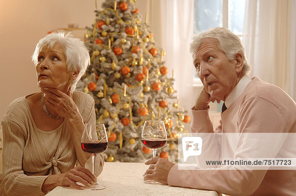 Mature couple sitting at a table with glasses of red wine  looking annoyed  in front of a Christmas tree