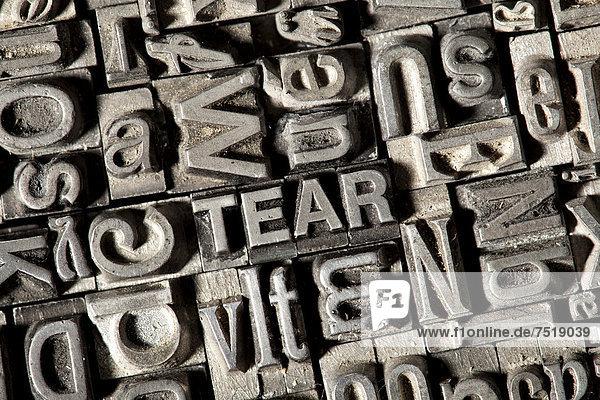 'Alte Bleilettern bilden das englische Wort ''TEAR'''