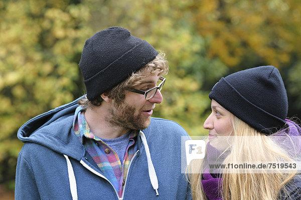 Ein junges Paar unterhält sich im herbstlichen Park  Baden-Württemberg  Deutschland  Europa  ÖffentlicherGrund