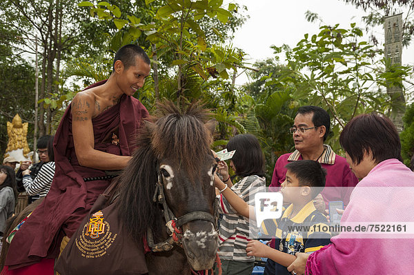 Buddhist monk on horseback collecting alms in the morning  temple and monastery of Wat Phra Archa Thong or Golden Horse Temple  Mae Chan  Chiang Rai Province  Northern Thailand  Thailand  Asia