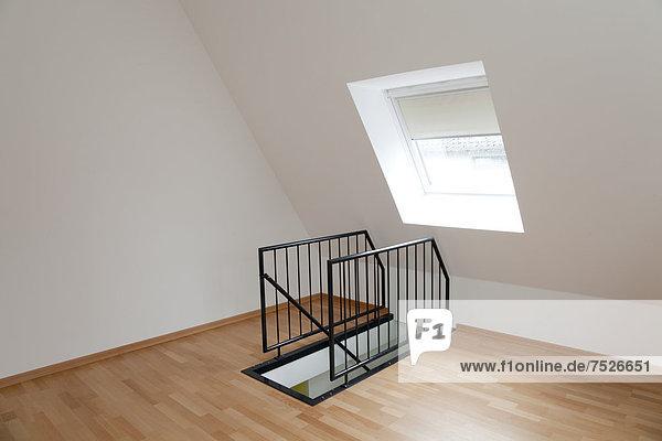 Leeres Zimmer im Dachgeschoss mit Treppengeländer