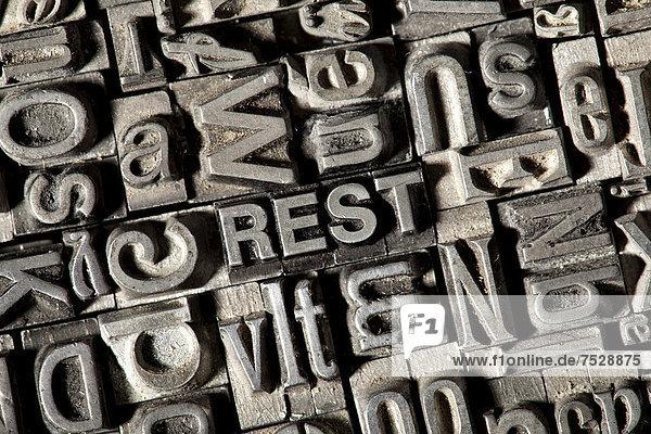 'Alte Bleilettern bilden das Wort ''REST'''