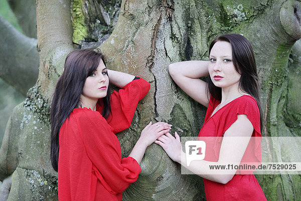 Two sisters in front of an old tree
