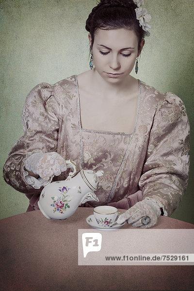 eine Frau in einem Epochenkleid schuettet Tee in eine Tasse
