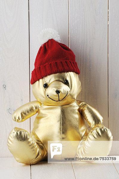 Golden teddy bear wearing a red cap