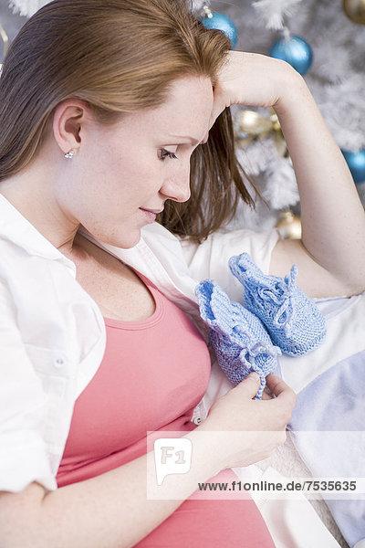 Schwangere Frau mit Babyschuhen vor einem Weihnachtsbaum
