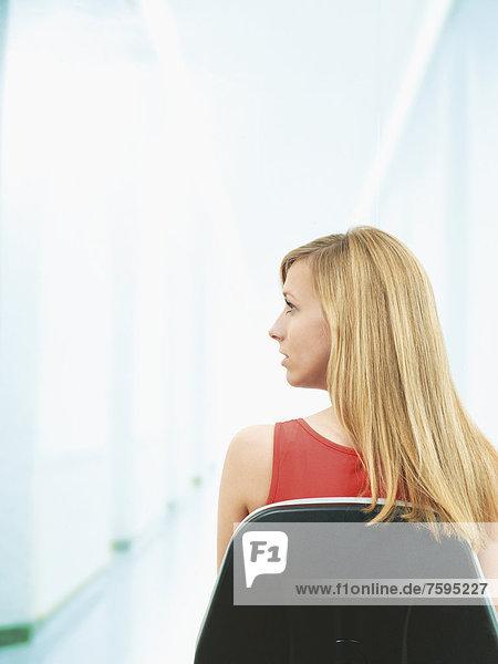 Junge Frau sitzt auf Stuhl  Rückansicht