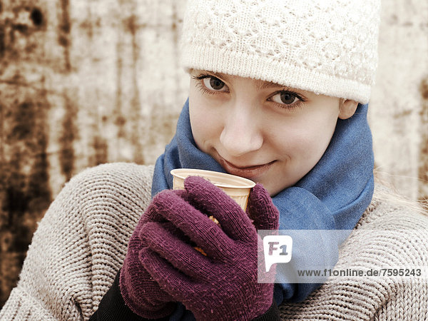 Girl wearing a hat and a scarf holding a cup