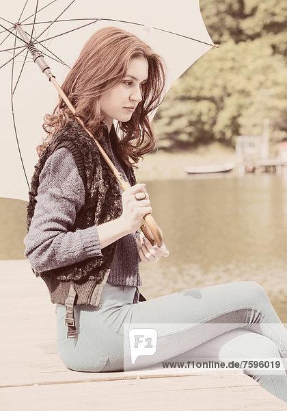 Junge Frau mit einem weißen Schirm sitzt an einem Bootssteg