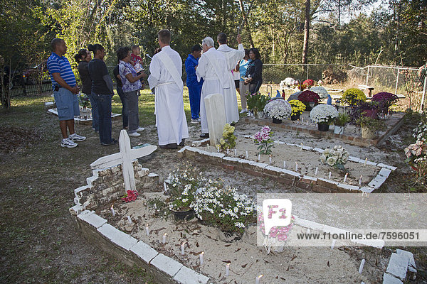 Fr. Kyle Dave leads the Blessing of the Graves at Ducre Cemetery on All Saints Day  with him are Deacon Steve Ferran and Deacon Bill Corry  Lacombe  Louisiana  USA