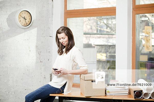 Geschäftsfrau mit Handy im Büro
