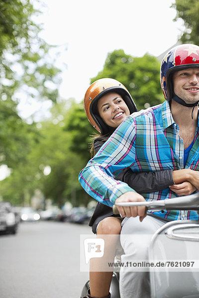 Paare fahren Roller zusammen