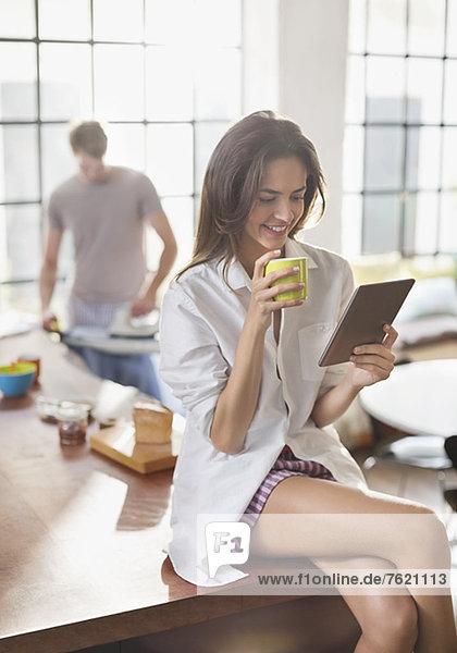 Frau mit digitalem Tablett in der Küche
