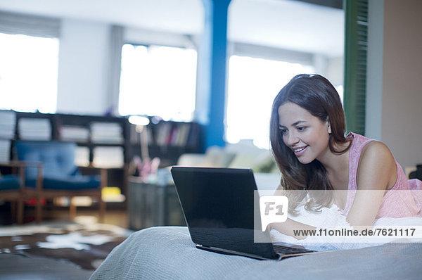 Frau mit Laptop auf dem Bett