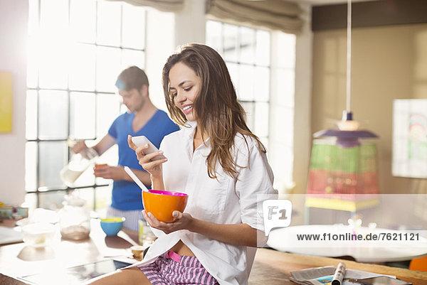Frau beim Frühstück mit dem Handy