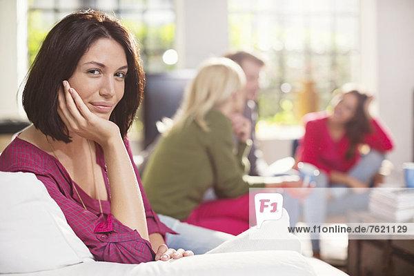 Lächelnde Frau auf dem Sofa sitzend