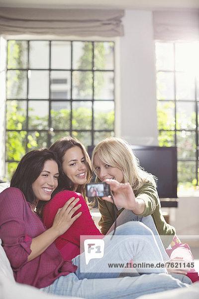 Frauen beim gemeinsamen Fotografieren auf dem Sofa