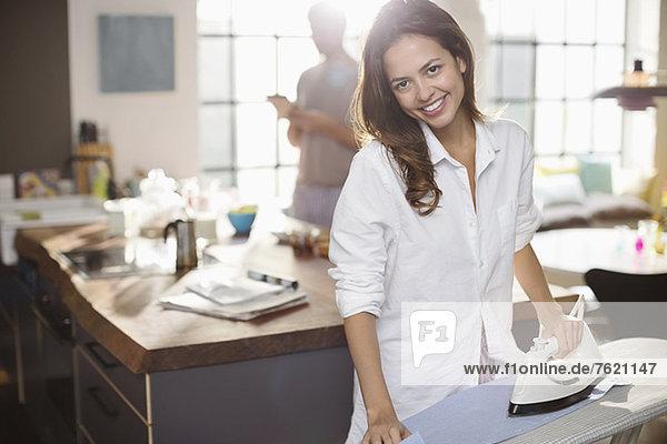Lächelnde Frau beim Bügeln in der Küche