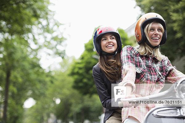 Frauen fahren gemeinsam auf dem Roller im Freien