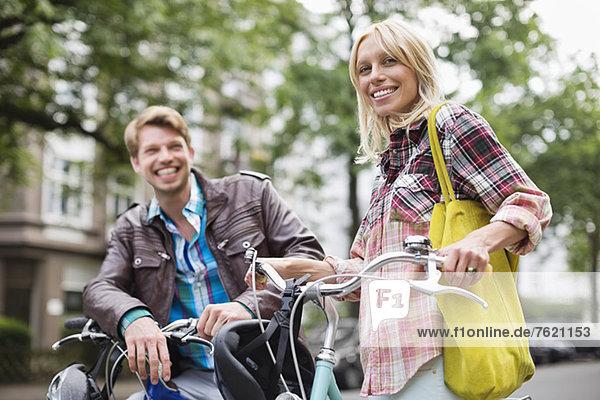 Paar steht auf Fahrrädern auf der Stadtstraße