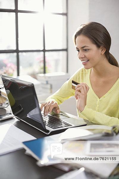 Frau beim Einkaufen auf dem Laptop