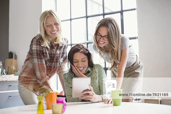 Frauen  die gemeinsam ein digitales Tablett benutzen