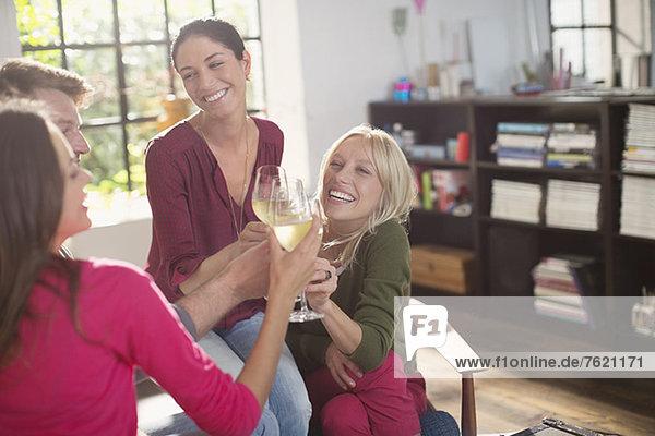 Freunde stoßen sich gegenseitig mit Weißwein an.