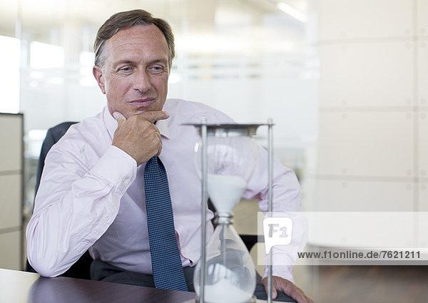 Geschäftsmann beobachtet Sanduhr im Büro