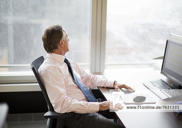 Geschäftsmann mit Blick aus dem Fenster im Büro