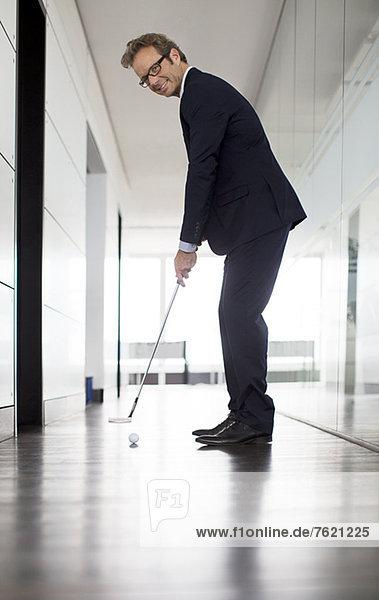 Geschäftsmann  der den Golfball ins Amt bringt.