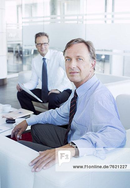 Geschäftsleute  die in der Büro-Lobby sitzen