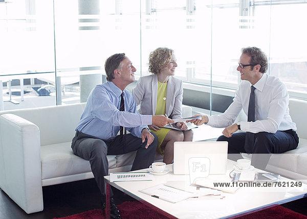 Geschäftsleute  die über den Lobbybereich im Büro sprechen