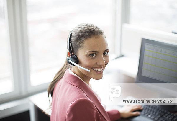 Geschäftsfrau mit Headset am Schreibtisch