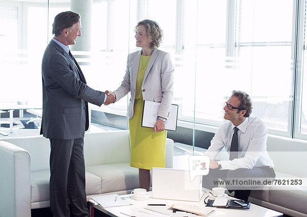Geschäftsleute beim Händeschütteln im Bürolobbybereich