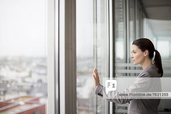 Geschäftsfrau am Bürofenster stehend