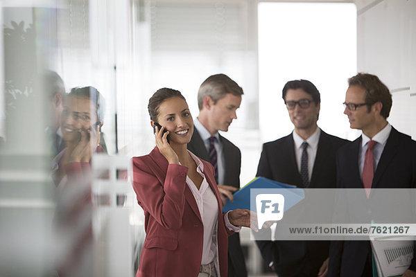 Geschäftsfrau beim Telefonieren im Büroflur
