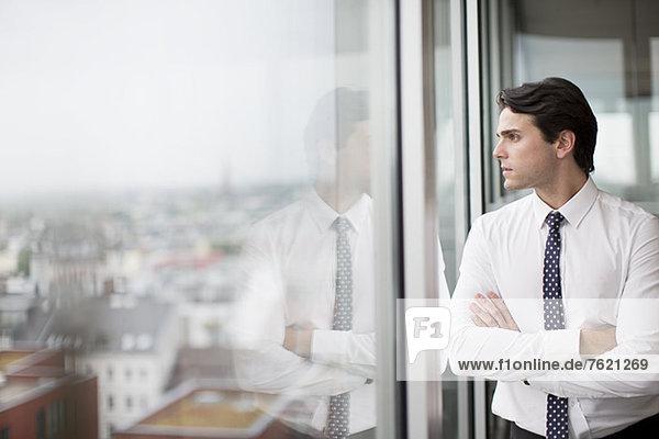 Geschäftsmann mit Blick aus dem Bürofenster