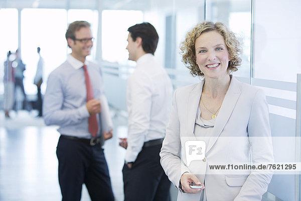 Geschäftsfrau lächelt im Büroflur