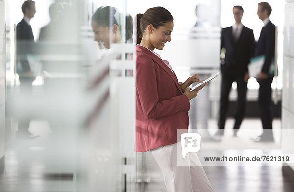 Geschäftsfrau mit digitalem Tablett im Büroflur