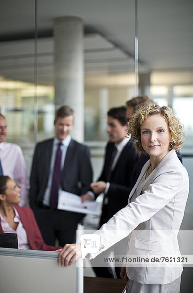 Businesswoman standing by cubicle in office