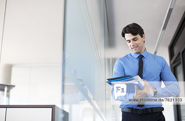 Geschäftsmann mit digitalem Tablett im Büroflur