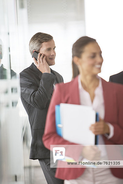Geschäftsmann beim Telefonieren im Büroflur