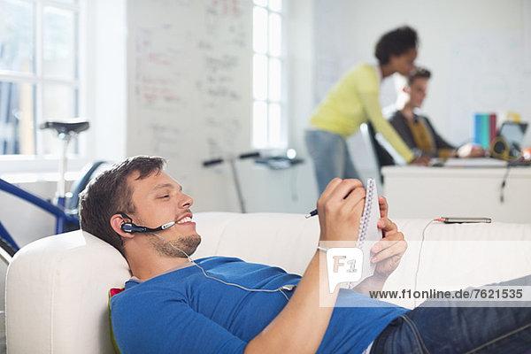 Mann im Headset beim Notieren auf dem Sofa
