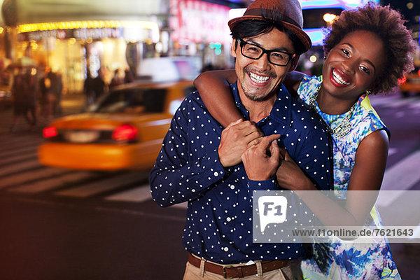 Paar lächelt nachts auf der Stadtstraße